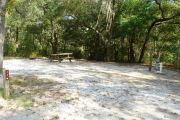 View of a vacant campsite with a picnic table, fire ring, electric pedestal, and water spigot. In the foreground is a brown site marker. A large tree is to the left of the post and the back edge is densely forested. The main part of the site is sandy with sparse vegetation and has partial shade.