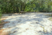 View of a vacant campsite with a picnic table, fire ring, electric pedestal, and water spigot. The back edge of the site is densely forested. The main part of the site is sandy with sparse vegetation and there is partial shade.