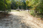 View of a vacant campsite with a picnic table, fire ring, electric pedestal and water spigot. The campsite is sandy with some vegetation. Trees line both sides of the campsite and the back of the site is densely forested. The campground bathroom is visible in the background.