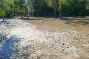 View of a vacant campsite with a picnic table, fire ring, electric pedestal and water spigot. Several wooden barricades are on the edges of the site. The main part of the site is grassy with some patches of sand. The back of the site is densely forested and there is partial shade.