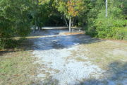 View of a vacant campsite with a picnic table, fire ring, electric pedestal, and water spigot. The main part of the site is sandy and hard packed in some areas. There are small trees and bushes on both sides of the site and there is partial shade.