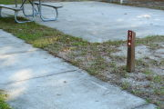 Close up of a brown site marker with an arrow on a wooden post. The site marker is to the right side of a sidewalk and a large concrete pad with a picnic table is present in the background.