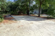 View of a vacant campsite with a picnic table, fire ring, electric pedestal, and water spigot. The site has a concrete side walk and camper pad. The sidewalk leads to the campsite and to the campground restroom. There are a few trees on the edges and partial shade. This site is ADA compliant.