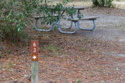 Close up of a brown site marker with an arrow on a wooden post. There is grass in the foreground and a picnic table in the background.