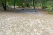 View of a vacant campsite with a picnic table, grill, and water spigot (this site does not have electricity).  The main part of the site is sandy with some patches of grass. There are trees spread throughout the site and there is partial shade.
