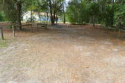 View of a vacant campsite with a picnic table, fire ring, and water spigot (this site does not have electricity). The main part of the site is sand and the edges of the site are lined with wooden barricades. There are trees scattered in the background and the campground restroom is behind the site.