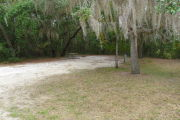 View of a vacant campsite with a picnic table, fire ring, electric pedestal, and water spigot. The main part of the site is sand with a large area of grass to the right side. There are two trees within the site and the back of the site is densely forested creating partial shade.