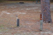 Close up of a brown site marker with an arrow on a wooden post. There is a water spigot to the left of the marker and a large tree directly behind it. A picnic table and fire ring is present in the background.