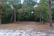 View of a vacant campsite with a picnic table, fire ring, water spigot, and electric pedestal. The main part of the site is sandy with patches of grass. There are several trees spread across the site and the back is densely forested creating partial shade.