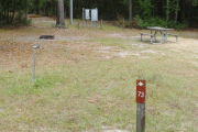 Close up of a brown site marker with an arrow on a wooden post. In the background a picnic table, water spigot, and fire ring are present. There are also two large grey electric boxes on the back edge of the site.