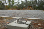 Side view of site sewer hook-up with fire ring and picnic table in the rear. Native plants and trees surround the site.