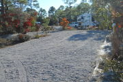 Front view of site 41 showing electric and water to the right, fire ring and picnic table to the left. Site is gravel. Site #59 can be seen in the rear. Site is surrounded by native vegetation.