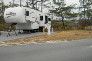 Side view of site #42 with a 40 ft Sundance 5th wheel with 2 slide outs. The rig is hooked up to the water, electric, and sewer, with picnic table in the left rear. Site is gravel and surrounded by native vegetation.