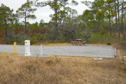 Side view of site showing electric, water, and sewer in the foreground, fire ring and picnic table in the background. Site is surrounded by native vegetation.