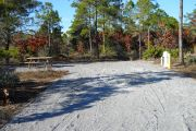 Front view of site #50 with the electric, water, and sewer on the right and picnic table on the left. Site is gravel and surrounded by native plants and trees.