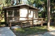 Cabin with concrete sidewalk and wheelchair accessible ramp leading to porch.