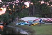 Photo: JONATHAN DICKINSON SP. The riverfront at Jonathan Dickinson State Park is shown in the golden sunset, as a man drags a kayak up the grassy bank in front of a line of beached canoes. His kayak has a bicycle strapped across the back of it. He is carrying a map.