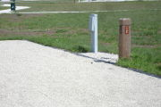 Photo: 012, Site number next to water and electric hooks ups at the back of a gravel site.