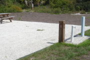 Photo: 025, Site number next to water and electric hooks ups at the back of a gravel site. A picnic table can be seen to the left.