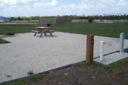Photo: 035, Site number next to water and electric hooks ups at the back of a gravel site. A picnic table, grill and fire ring can be seen on the left.