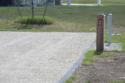 Photo: 044, Site number next to water and electric hooks ups at the back of a gravel site. A restroom is nearby.