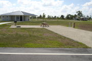 Photo: 044, Campsite with picnic table, grill and fire ring on the left and water and electric on the left. A restroom is nearby.