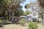 A view of the Histroic Koreshan Settlement on Earth Day 2010, with visitors stopping by the many exhibitors tents present on the ground or sitting in the shade to listen  one of the bands on the covered stage.