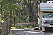 A small motor home sits squarely on campsite number ten, adjacent to a picnic table and rustic wooden fencing, at Lake Griffin State Park