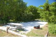 Photo: 021, With the picnic table and fire ring in the front, the shadows from the buttonwood trees around the site cover the sand.