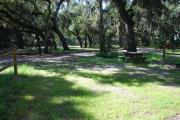 This is a picture of campsite 13 from the back of the site looking toward the road.   The site has water and 50amp electric service.  This is a sunny site with a gravel foundation.  The site has a picnic table and a ground campfire ring.