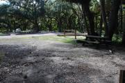 This is a picture of campsite 22 from the back of the site looking toward the road.   The site has water and 50amp electric service.  This is a partly sunny site with a gravel foundation.  The site has a picnic table and a ground campfire ring.