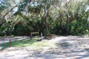 Campsite 27 is a partial sunny site with a gravel foundation located on the right hand side of the road.  Looking into the site on the right is the water and 50amp electrical service. There is a picnic table and ground campfire ring.  At the front left side of the site is the brown site marker.