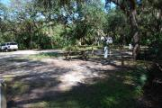 This is a picture of campsite 27 from the back of the site looking toward the road.   The site has water and 50amp electric service.  This is a partly sunny site with a gravel foundation.  The site has a picnic table and a ground campfire ring.