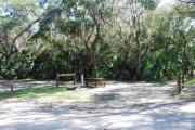 This is a picture of campsite 27 looking from the road into the partly sunny site.  This site has 50amp service and water hookups.  There is a gravel foundation with a picnic table and a ground campfire ring.