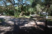 This is a picture of campsite 28 from the back of the site looking toward the road.   The site has water and 50amp electric service.  This is a partly sunny site with a gravel foundation.  The site has a picnic table and a ground campfire ring.