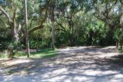 Campsite 29 is a partial sunny site with a gravel foundation located on the right hand side of the road.  Looking into the site on the right is the water and 50amp electrical service. There is a picnic table and ground campfire ring.  At the front left side of the site is the brown site marker.