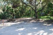 Campsite 32 is a partial sunny site with a gravel foundation located on the right hand side of the road.  Looking into the site on the right is the water and 50amp electrical service. There is a picnic table and ground campfire ring.  At the front left side of the site is the brown site marker.