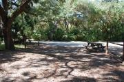 This is a picture of campsite 32 from the back of the site looking toward the road.   The site has water and 50amp electric service.  This is a partly sunny site with a gravel foundation.  The site has a picnic table and a ground campfire ring.