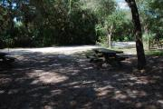 This is a picture of campsite 33 from the back of the site looking toward the road.   The site has water and 50amp electric service.  This is a partly sunny site with a gravel foundation.  The site has a picnic table and a ground campfire ring.