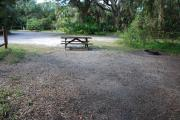 This is a picture of campsite 37 from the back of the site looking toward the road.   The site has water and 50amp electric service.  This is a partly sunny site with a gravel foundation.  The site has a picnic table and a ground campfire ring.