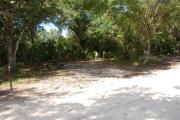 This is a picture of campsite 43 looking from the road into the partly sunny site.  This site has 50amp service and water hookups.  There is a gravel foundation with a picnic table and a ground campfire ring.