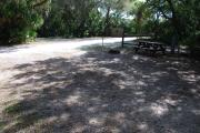 This is a picture of campsite 47 from the back of the site looking toward the road.   The site has water and 50amp electric service.  This is a partly sunny site with a gravel foundation.  The site has a picnic table and a ground campfire ring.