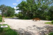 This is picture of campsite #51 from the back of the site looking toward the road.  Site has 50amp electric, water and sewage hook-ups.  This is a sunny site with stone foundation and vegetation on sides.  There is a separate section to the side with the picnic table, cooking grill and ground campfire ring.