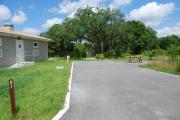Campsite #61 is an ADA accessible, sunny site with asphalt pavement and vegetation on sides located on the right hand side of the road that has to be driven straight into.  Looking into the site on the left are the water, 50 amp electric and sewage hook-ups. Also, to the left is a sidewalk to the restroom that is next to the site. To the right is a separate section containing an ADA accessible picnic table, cooking grill and ground campfire ring.  At the front left side of the site is the brown site marker.