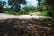 This is picture of campsite #73 from the back of the site looking toward the road.  Site has 50amp electric, water and sewage hook-ups.  This is a partial shady site with stone foundation and vegetation on sides.  There is a separate section to the side with the picnic table, cooking grill and ground campfire ring.