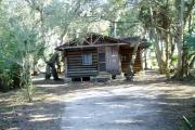 This is a front view picture of Cabin 3 which is a rustic palm log cabin built by the Civilian Conservation Corp. in the mid 1930's.  There is a living/dining/bedroom area with 2 double beds, a sofa bed, dining set, linen cabinet and fireplace.  There also is a bathroom and a kitchen with coffee maker, toaster, microwave, range, refrigerator, dishes, silverware and cooking utensils.  The cabins sleep up to six.  Off of the back porch there is a fire ring, cooking grill and a picnic table.  There are no pets and no smoking allowed in the cabins.