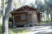 This is a front view picture of Cabin 5 which is a rustic palm log cabin built by the Civilian Conservation Corp. in the mid 1930's.  There is a living/dining/bedroom area with 2 double beds, a sofa bed, dining set, linen cabinet and fireplace.  There also is a bathroom and a kitchen with coffee maker, toaster, microwave, range, refrigerator, dishes, silverware and cooking utensils.  The cabins sleep up to six.  Off of the back porch there is a fire ring, cooking grill and a picnic table.  There are no pets and no smoking allowed in the cabins.