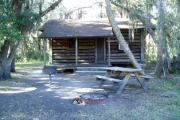 This is a back porch view picture of Cabin 5 which is a rustic palm log cabin built by the Civilian Conservation Corp. in the mid 1930's.  There is a living/dining/bedroom area with 2 double beds, a sofa bed, dining set, linen cabinet and fireplace.  There also is a bathroom and a kitchen with coffee maker, toaster, microwave, range, refrigerator, dishes, silverware and cooking utensils.  The cabins sleep up to six.  Off of the back porch there is a fire ring, cooking grill and a picnic table.  There are no pets and no smoking allowed in the cabins.