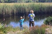 Two young boys fish from the bank on Tide Creek, a tide-influenced tributary to greater Ochlockonee River.