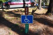 A rustic 4 feet by 4 feet wood post with signage designating Site 24 as a full access ADA site.